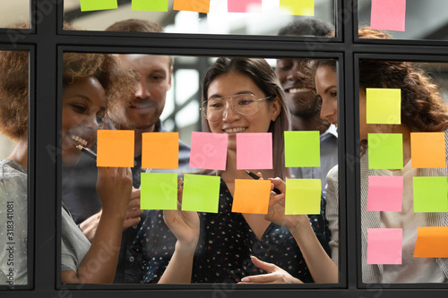 Fototapeta Smiling multiethnic colleagues brainstorm using post it stickers obraz