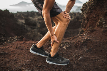 Male runner holding injured calf muscle and suffering with pain. Sprain ligament while running outdoors. Close-up legs view.