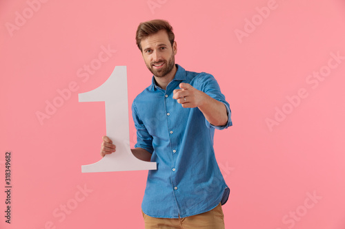 Obraz happy casual guy holding number one sign and pointing finger - fototapety do salonu
