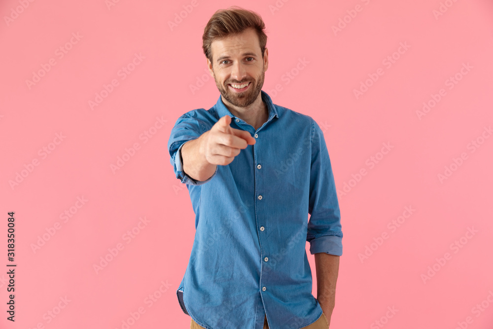 Fototapeta happy casual man in denim shirt smiling and pointing finger