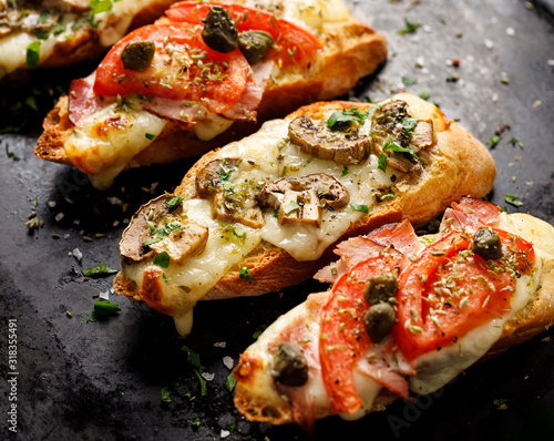 Fototapeta Grilled bruschetta with the addition of tomatoes, capers, ham, mushrooms and herbs on a black background, close up obraz