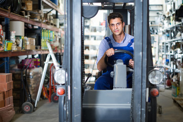 working man in unifom is using сargo moving machine in the building store