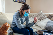 Ill Woman Checking Thermometer Having Fever. Girl Wearing Protective Mask While Having Cold, Flu At Home. Healthcare