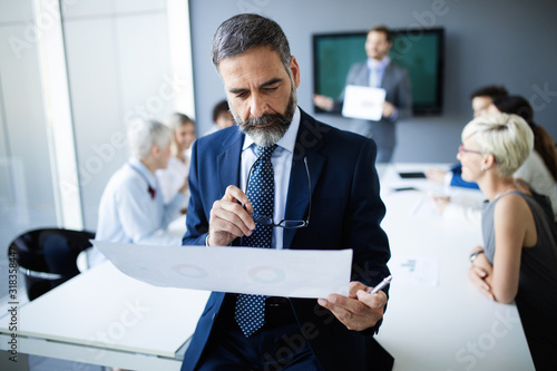 Photo Shot of thinking financial advisor businessman working in office.