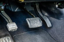 Focus On Parking Brake Of Vehicle With Gas And Brake Pedals In The Background