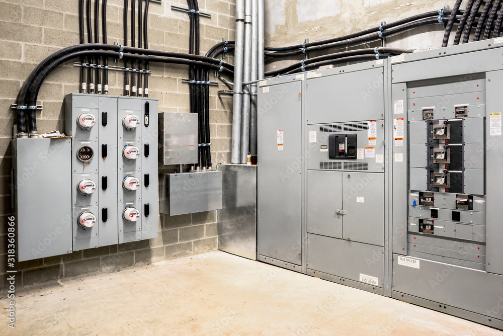 Fototapeta Electrical room of residential or commercial building. Multiple smart meters, main power breaker, meter stacks and cabinets. Perspective view