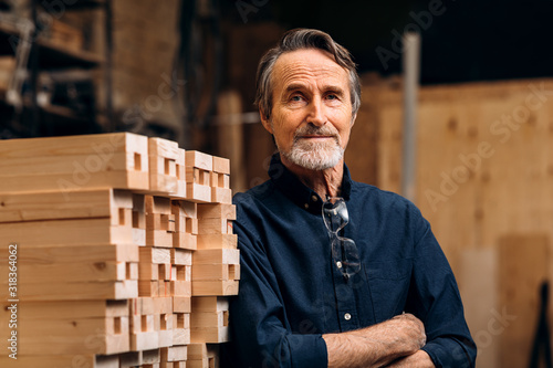 Obraz Portrait of confident senior male carpenter standing in his workshop - fototapety do salonu