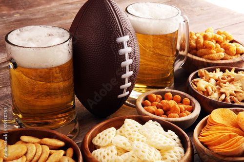 Chips, salty snacks, football and Beer on a table. Great for Bowl Game snack projects. - 318370253