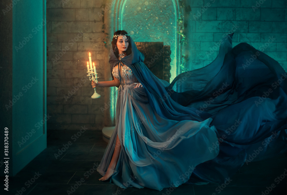 Fototapeta Luxury lady Queen medieval royal dress run escapes from Gothic night castle. Blue silk dress, cloak train plume waving motion. Holds in hands old candlestick burning candles. Background old retro room