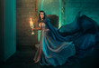 Luxury lady Queen medieval royal dress run escapes from Gothic night castle. Blue silk dress, cloak train plume waving motion. Holds in hands old candlestick burning candles. Background old retro room
