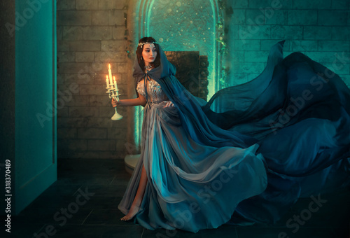 Obraz Luxury lady Queen medieval royal dress run escapes from Gothic night castle. Blue silk dress, cloak train plume waving motion. Holds in hands old candlestick burning candles. Background old retro room - fototapety do salonu
