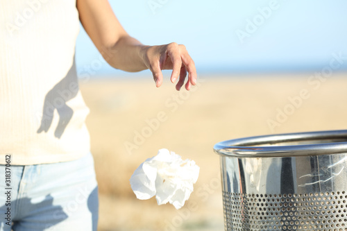 Fotografie, Tablou Woman hand throwing trash at the floor on the beach