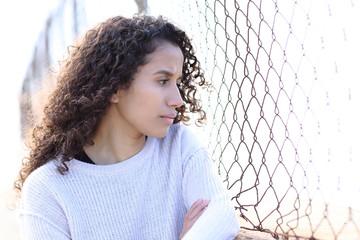 Serious latina girl looking away in the street