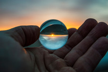 Glass Ball In Hand On Sunset