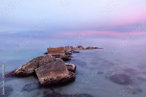 Sunset on the beach of Aguamarga, Alicante. Pastel colors of a sunset on the beach with sea rocks of protagonists in the foreground. Perfect for background.