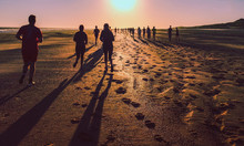 Silhouette People Walking At Beach Against Sky During Sunset