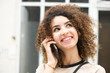 Close up smiling young woman with curly hair talking with cellphone and looking away