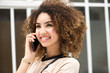 Close up happy young woman with curly hair talking with mobile phone and looking away