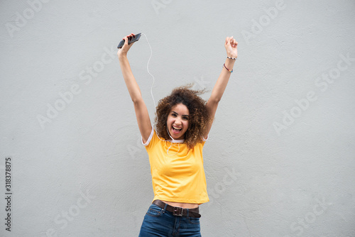 happy young woman with arms raised holding cellphone and listening to music by gray background