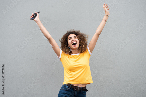Photo happy young woman with arms raised holding mobile phone and listening to music b