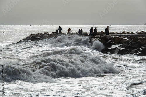 People looking  at stormy sea Poster Mural XXL