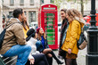 A group of young friends talk and laugh happily in a London street