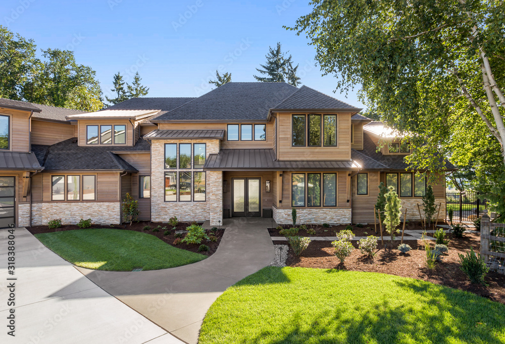 Fototapeta Luxury home exterior on sunny day with blue sky. Features three car garage, large driveway, and elegant design