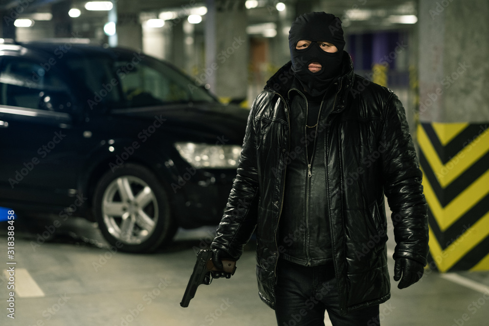 Fototapeta Terrorist or gangster in black jacket, gloves and balaclava holding handgun