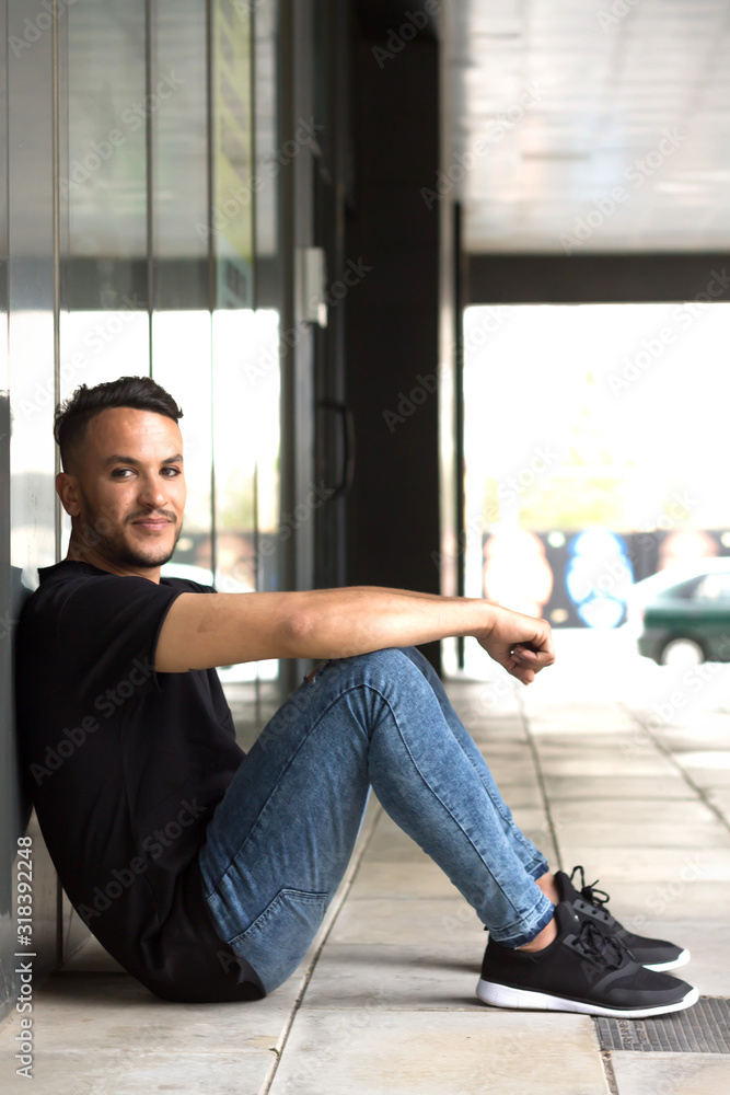 Fototapeta Portrait Of Handsome Man Sitting By Wall