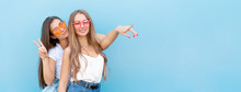 Two Young Hipster Woman Friends In Retro Neon Sunglasses Standing And Smiling Over Blue Wall