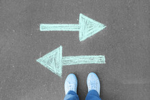 Person Standing On Road With Arrows Pointing In Different Directions. Concept Of Choice