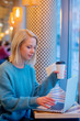 Leinwanddruck Bild - blonde woman drink coffee and working with laptop computer in a the cafe