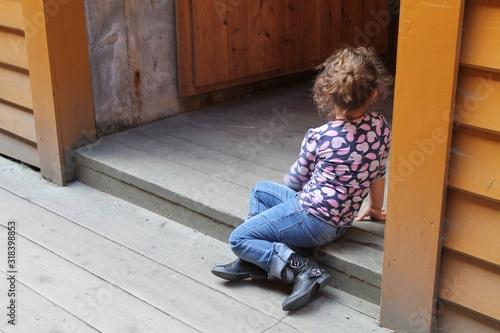 Full Length Of Girl Sitting At Door Canvas Print