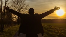 Rear View Of Silhouette Man With Arms Outstretched Standing On Field Against Sky During Sunset