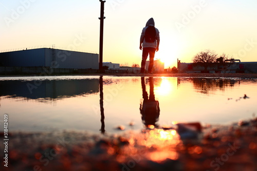 Fotografia REFLECTION in puddle in city DURING SUNSET