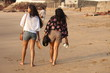 Rear View Of Women Walking At Sandy Beach