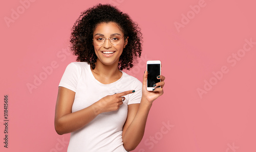 Smiling afro girl showing empty screen of mobile phone. Wallpaper Mural