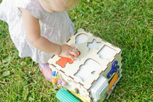 Girl Inserts A Bear Figurine Into Hole Of Learning Resources Sorting Cube, Fine Motor Toy, Early Number, Patterns. Developing Games For Children. Busy Board.