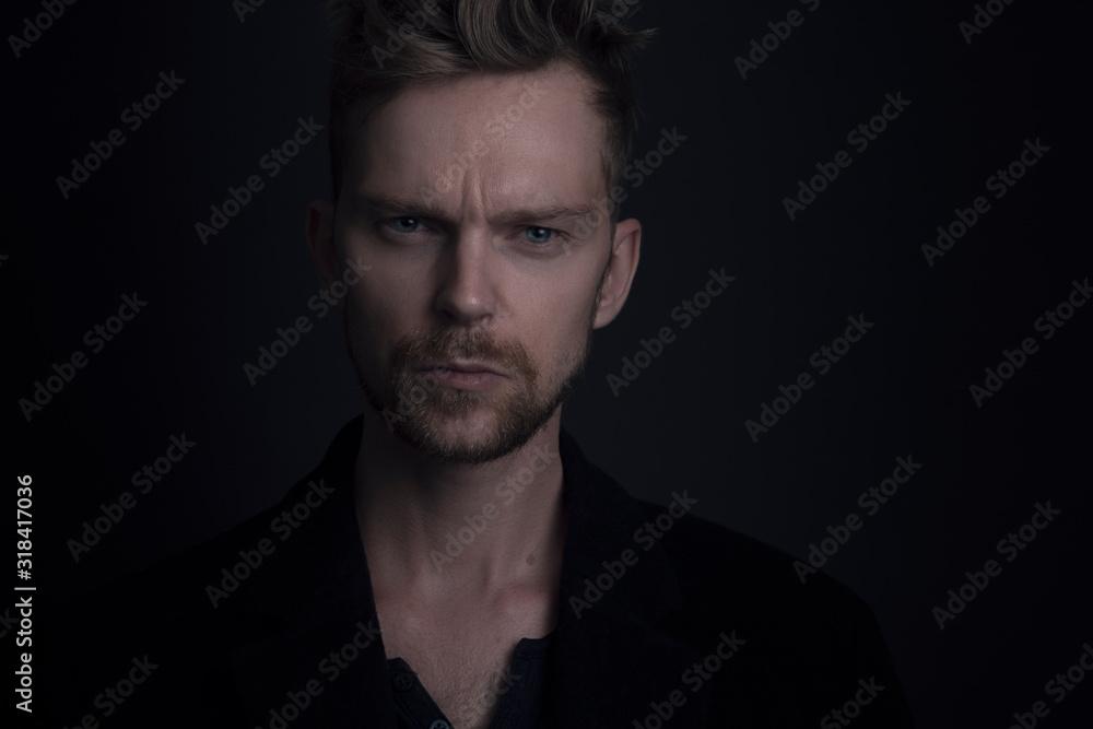 Fototapeta Close-Up Portrait Of Serious Man Against Black Background