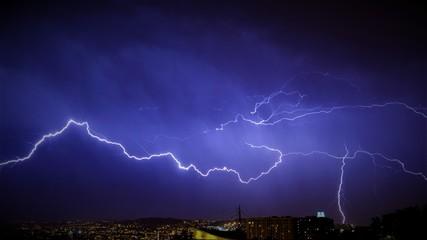 LIGHTNING IN SKY OVER CITY AT NIGHT
