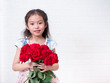 Happy Asian little cute girl standing and holding red rose bouquet over white bricks wall background.