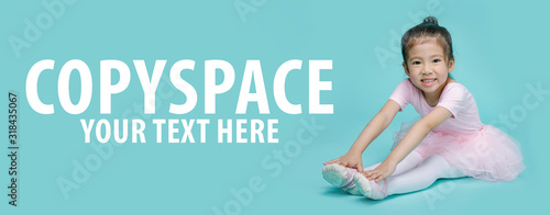 Beautiful smiling Asian little girl in a pink suit is dancing a ballet at school, empty space in studio shot isolated on colorful blue long banner background