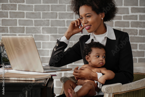 Fototapeta african american business woman taking care of her baby boy while working at home obraz