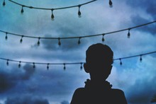 Rear View Of Silhouette Boy Against Sky