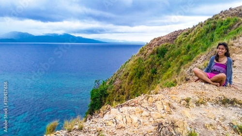 Fotografie, Obraz WOMAN SITTING ON cliff by sea