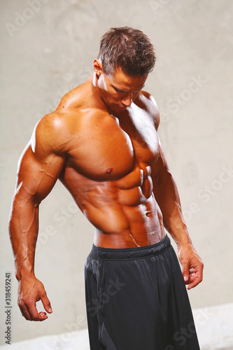 Strong muscular man bodybuilder poses and shows his muscles Canvas Print