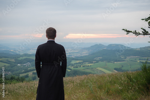 Fotografia, Obraz REAR VIEW OF PRIEST OUTDOORS