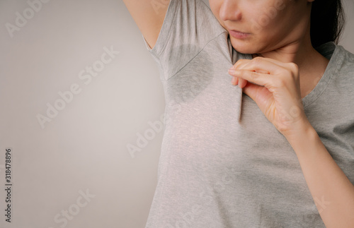 Photo Attractive woman embarrassing on her sweat stain on her gray t-shirt