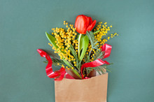 Mimosa And Red Tulip Flowers Bunch With Bow On White Paper Envelope On Green Background
