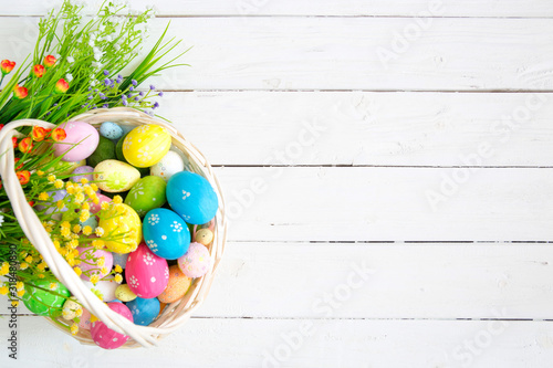 Colorful easter eggs in basket and flowers on white wooden table Canvas Print